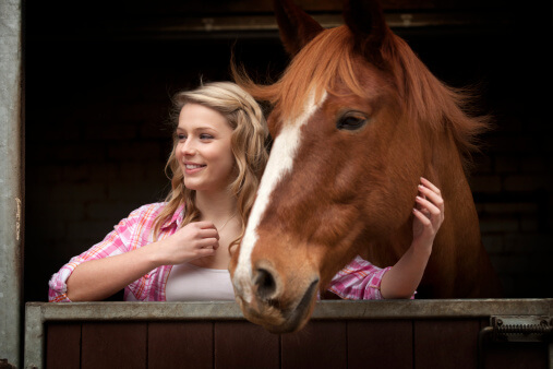 Young woman petting a horse during equine therapy for addiction treatment.
