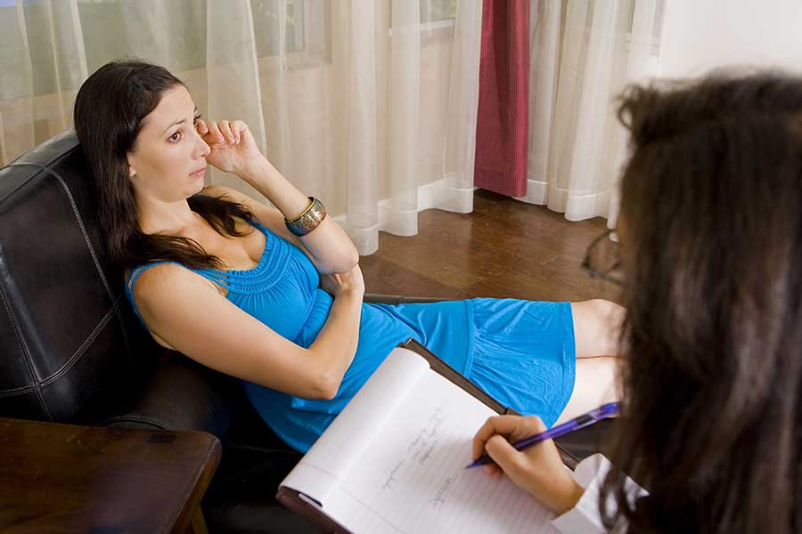 Counselor conducting cognitive behavioral therapy with addiction patient.